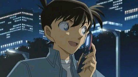 携帯で電話をする新一